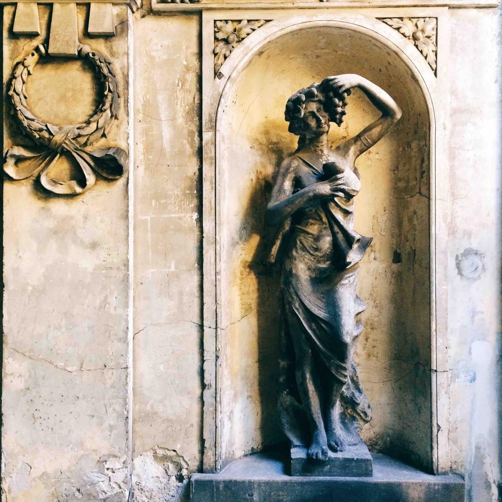 Via Tigor 12 statua di donna con grappolo d'uva in una mano