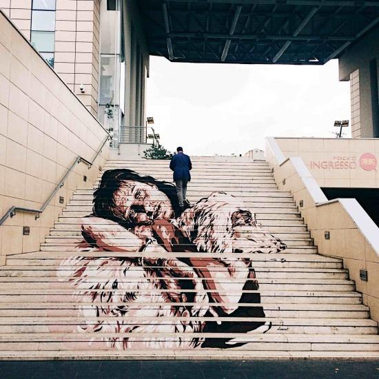 scalinata esterna mercato trionfale con opera di Anna Magnani nero bianco e rosso dello street artist Diavù