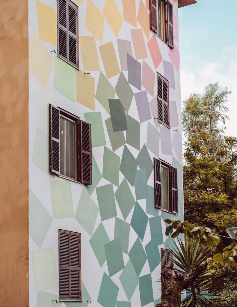 street art su facciata di un palazzo con cubi colorati su sfondo bianco