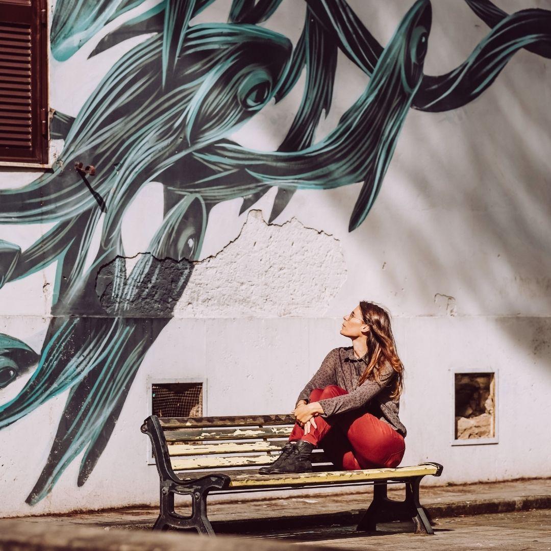 ragazza ammira opera di street art che rappresenta balene che nuotano a tor marancia