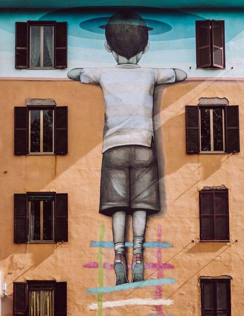 murales di bambino che si arrampica su scaletta a tor marancia roma