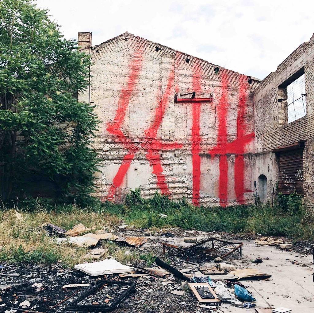 la firma dell'artista scritta a caratteri enormi su un'intera parete dell'edificio dell' ex mira lanza con vernice rossa