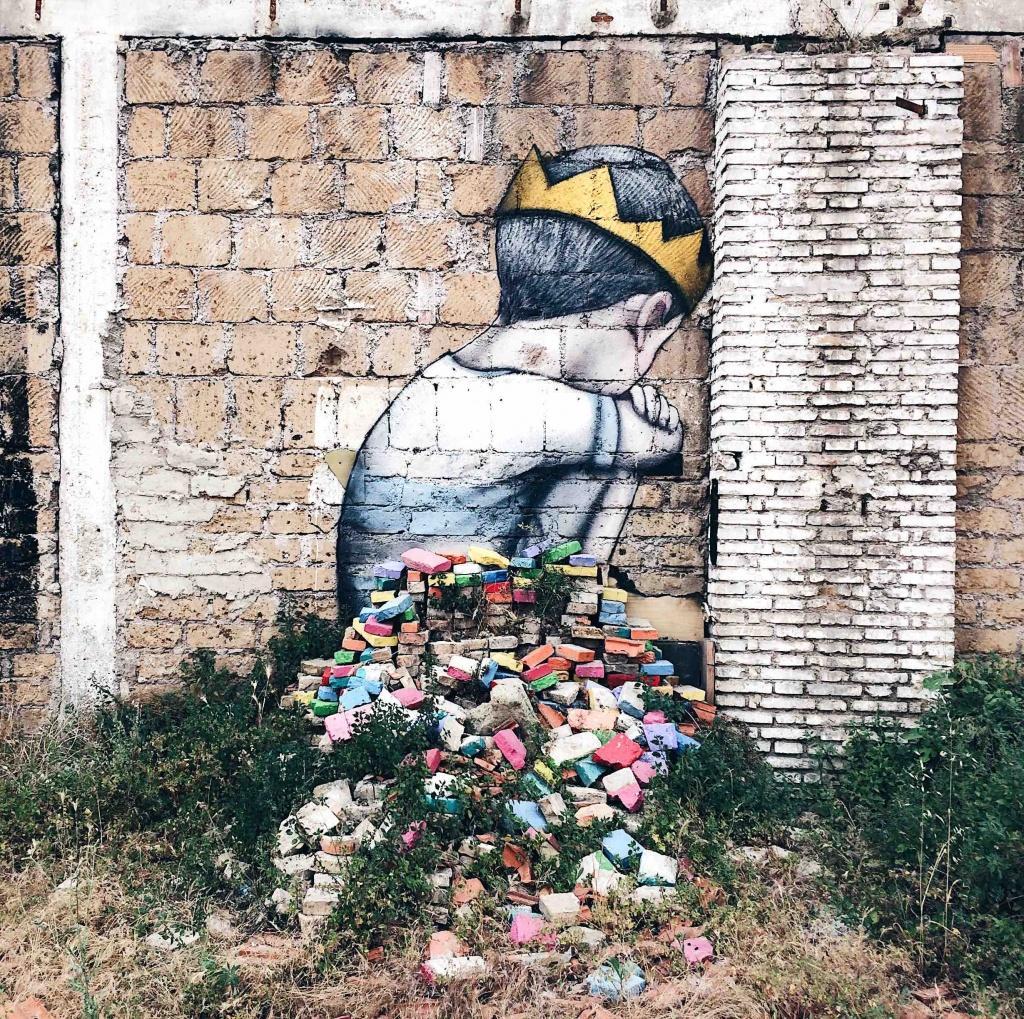 opera dell'artista francese Seth che rafficura un bambino seduto di spalle su un cumulo di mattoni colorati