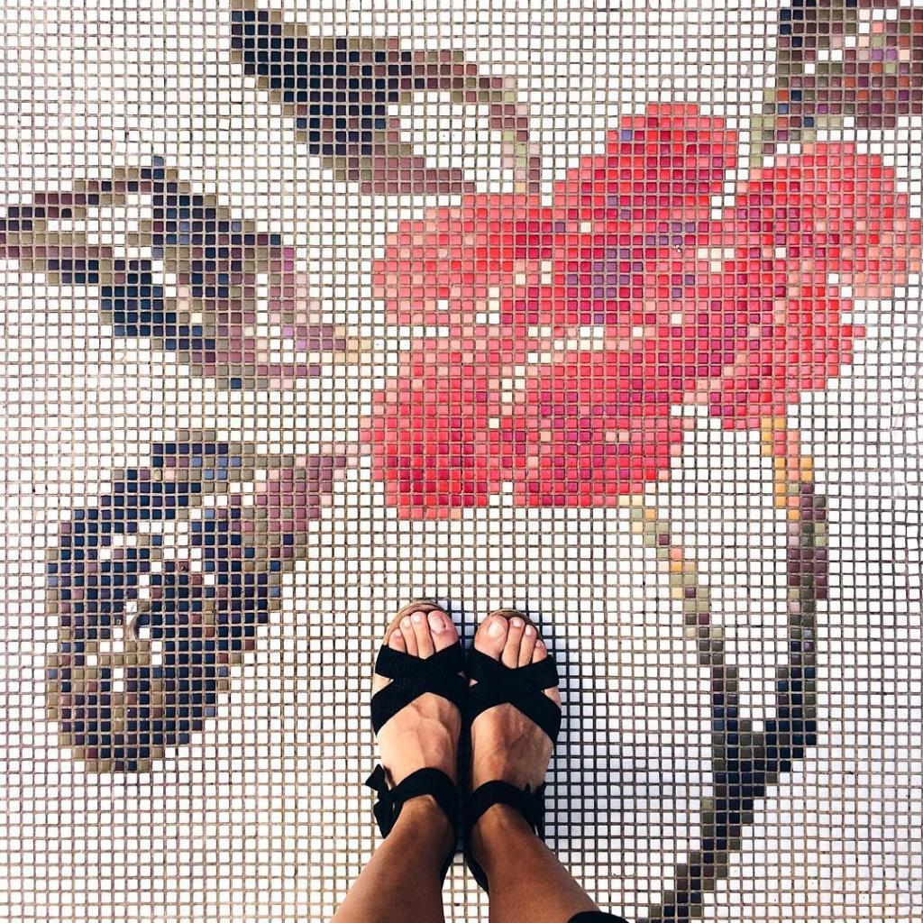 Dettaglio di un pavimento a mosaico con il disegno di un grande fiore rosso