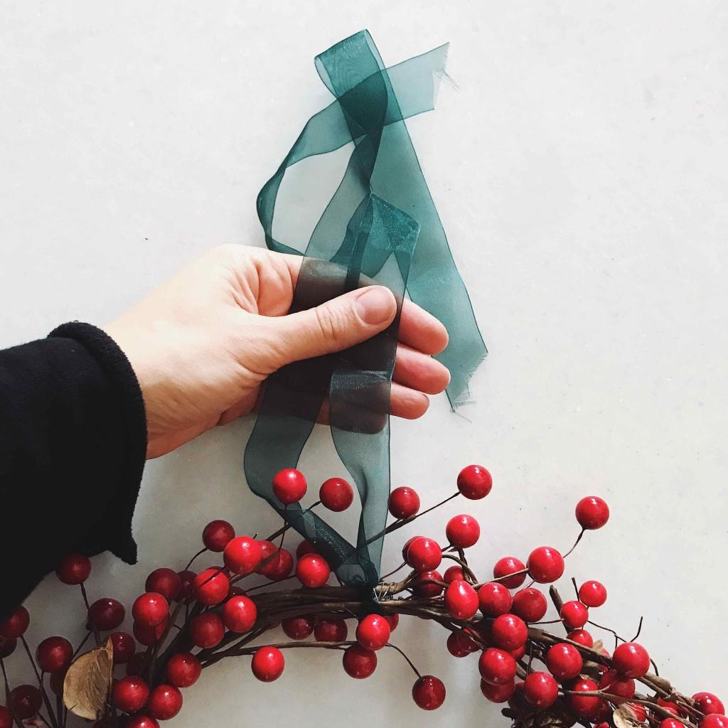 Come fare una ghirlanda natalizia in pochi minuti: fissare un nastro per appenderla
