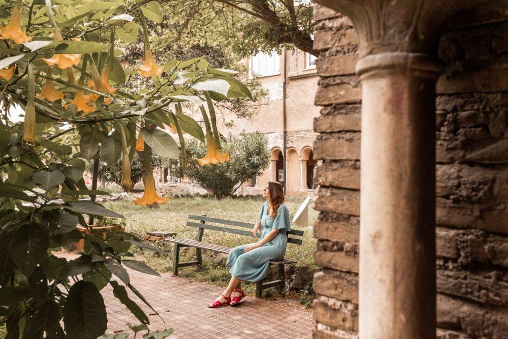 ragazza seduta su panchina in un antico giardino