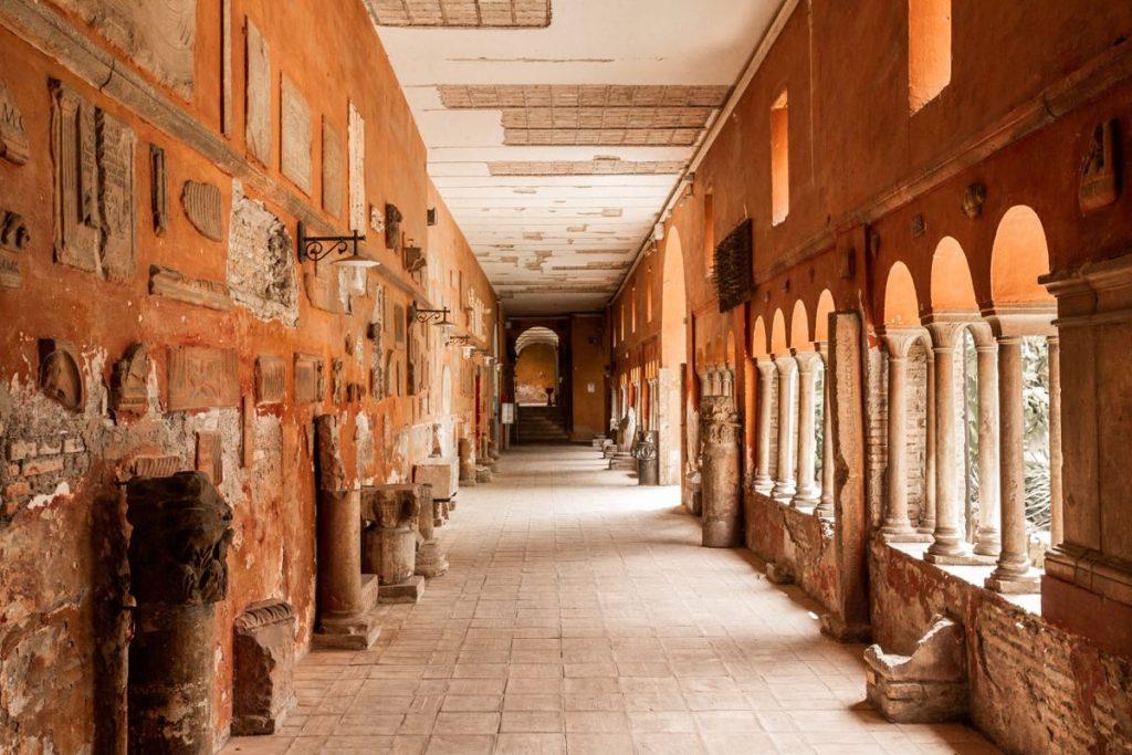 corridoio di antico chiostro di Trastevere con lapidi e colonne antiche