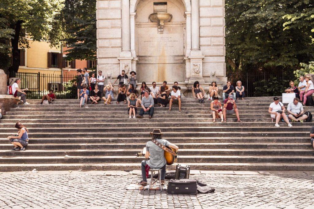 uomo seduto di spalle suona chitarra davanti a persone sedute su gradinata