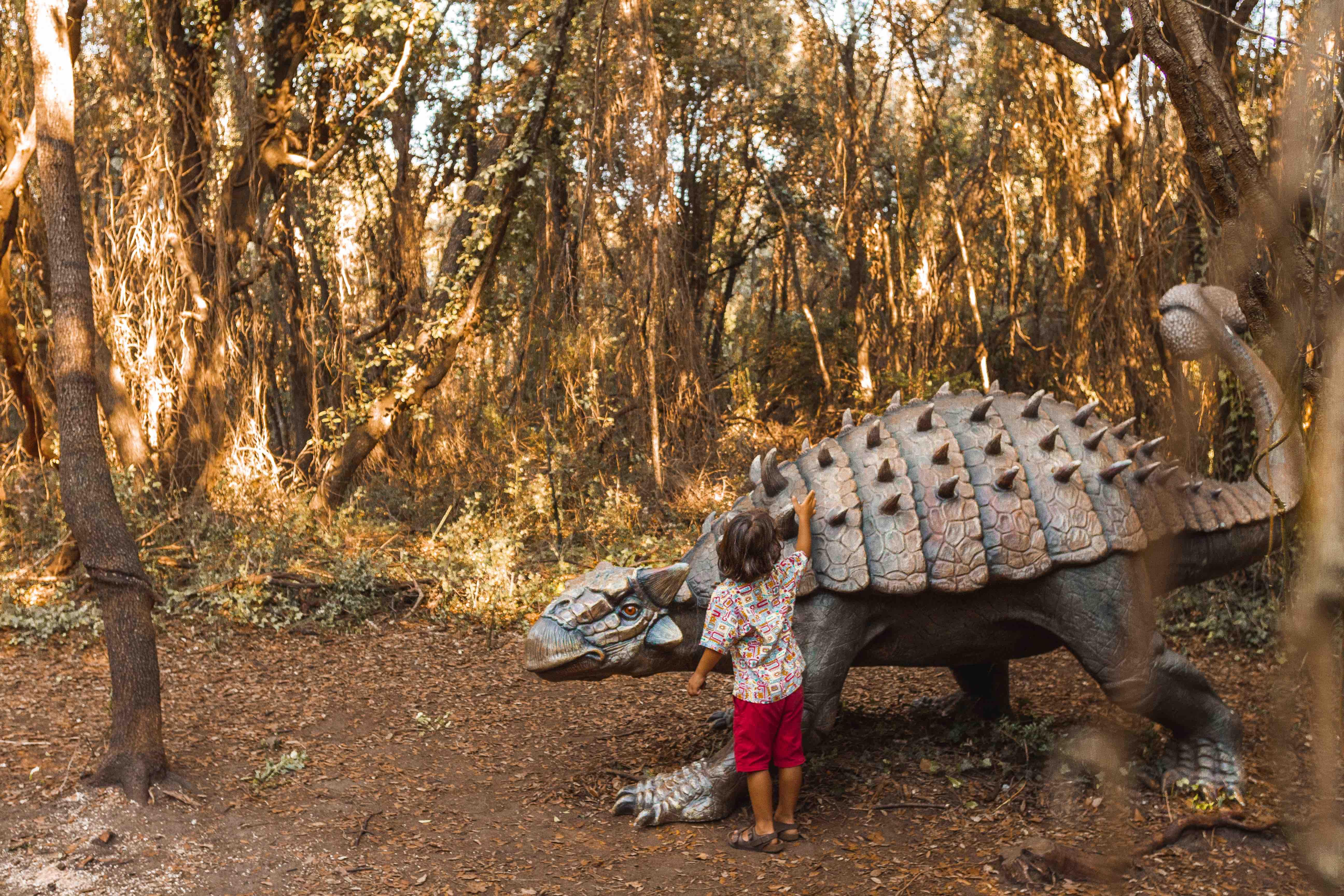 Bambino tocca dinosauro nel bosco: visita alla mostra I dinosauri in carne e ossa