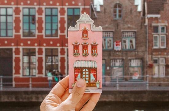2 giorni a Bruges: case a gradoni e mano che tiene souvenir a forma di casa