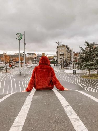2 giorni a Copenhagen: ragazza di spalle con cappotto rosso in parco urbano