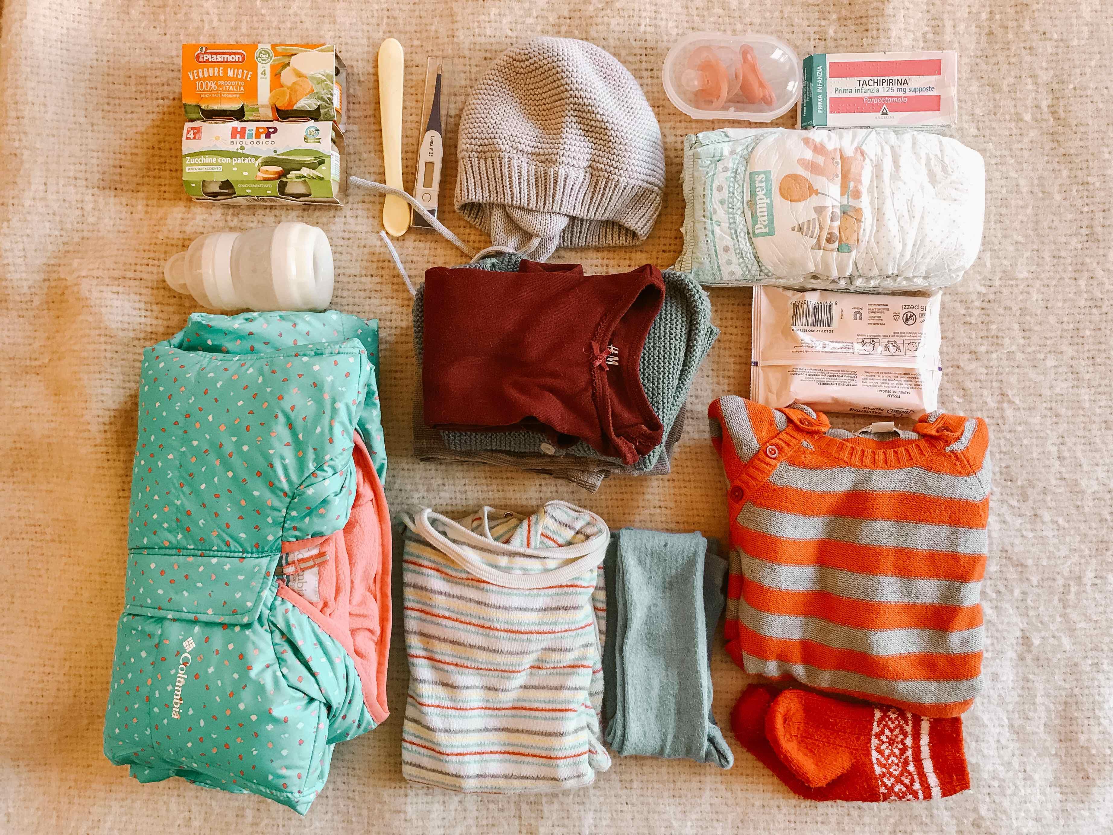 Cosa ho messo nello zaino: vestiti e accessori per bambini piegati sul letto