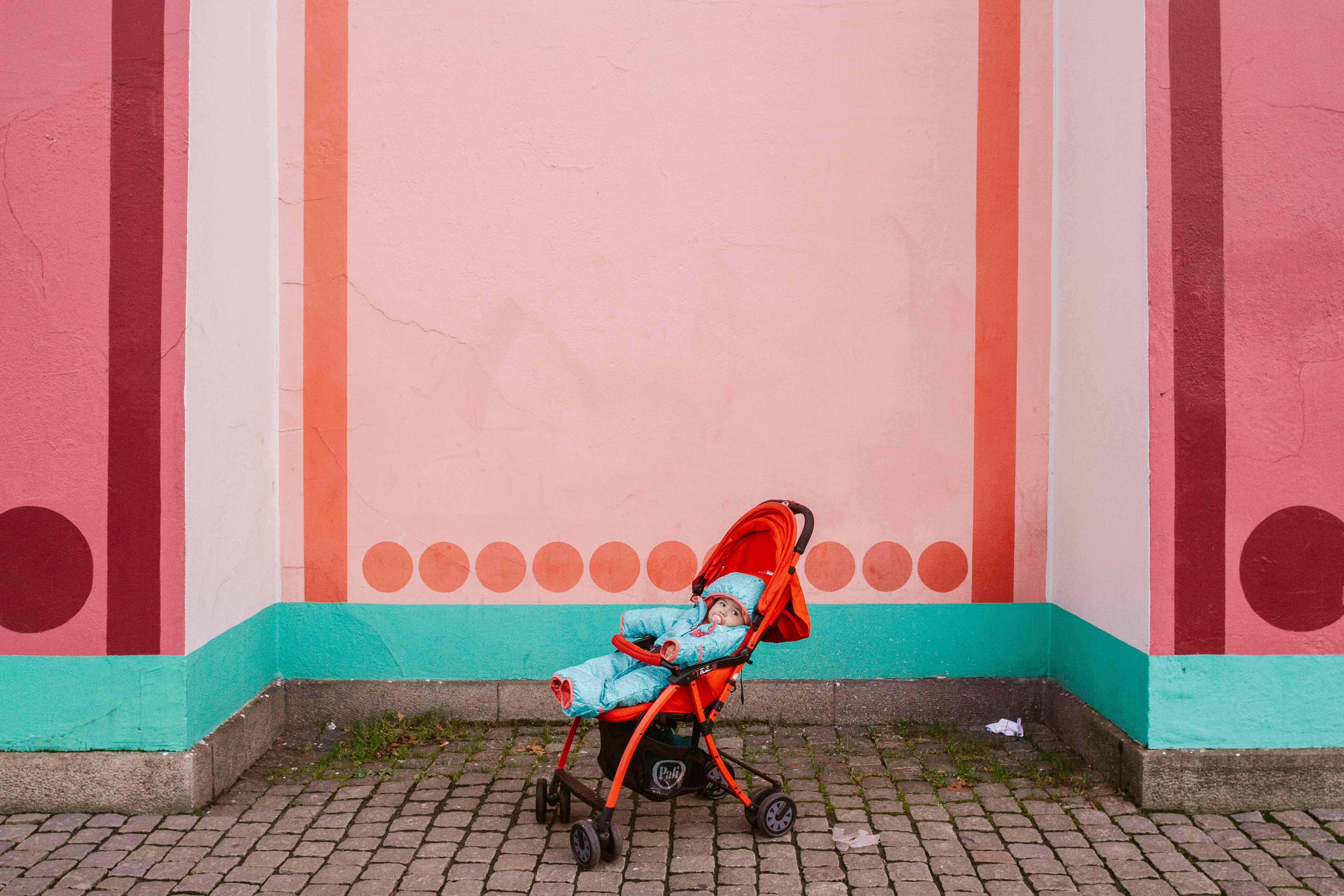 viaggiare da sola con mia figlia: bambina piccola nel passeggino davanti a parete rosa
