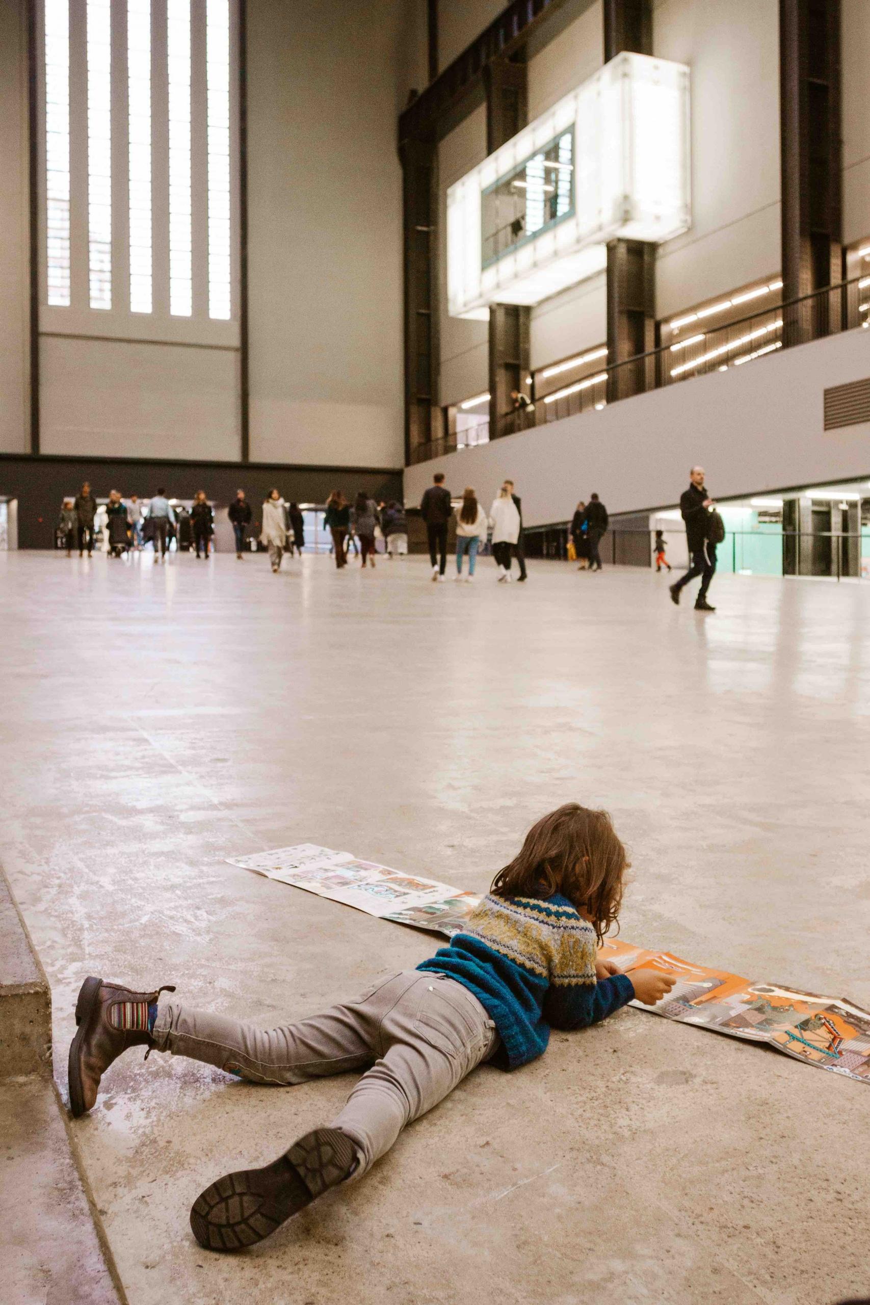 bambino disteso con libro davanti alla galleria Tate Modern