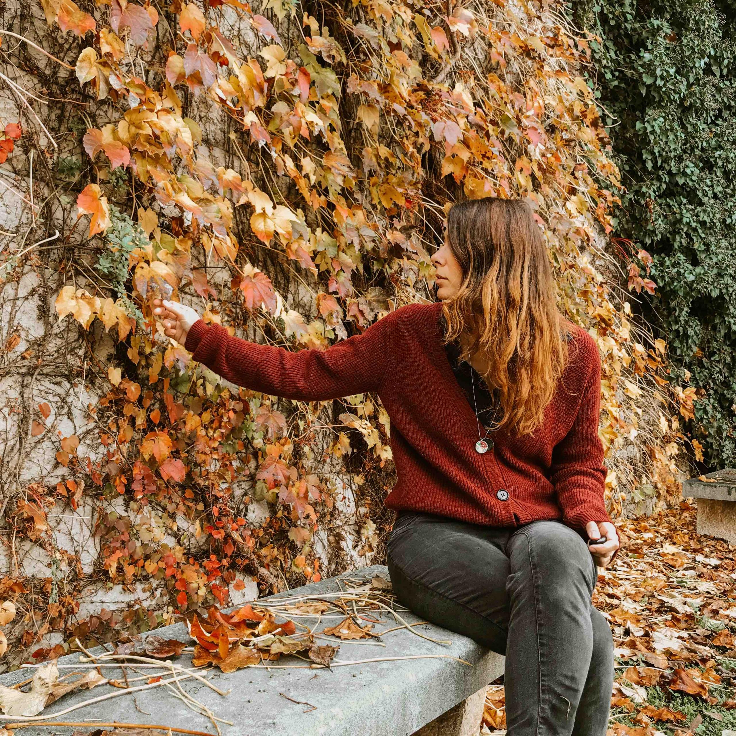 ragazza seduta su panchina foglie gialle e rosse dietro