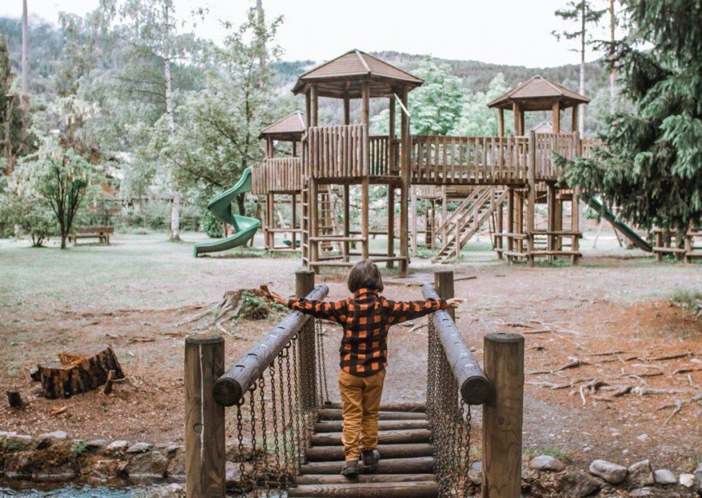 bambino gioca su giochi di legno nel bosco