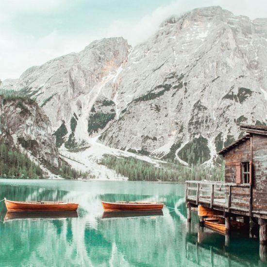 due barche su lago di braies con acqua colo r verde e montagna sullo sfondo