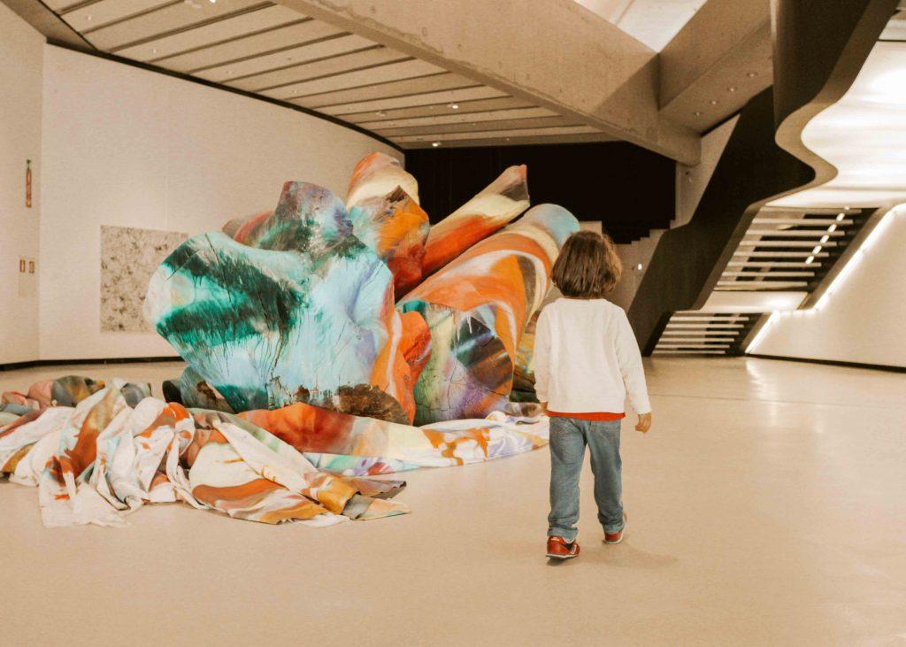 bambino davanti a opera di arte contemporanea