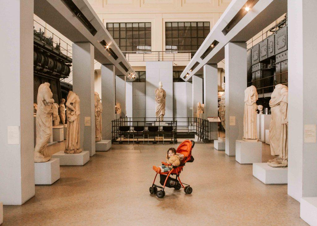 bambina nel passeggino tra sculture antiche