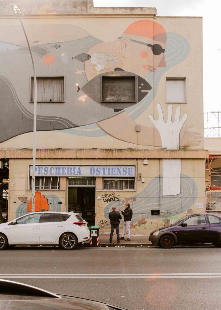 Murales su parete gialla di uomo che nuota Agostino Iacurci