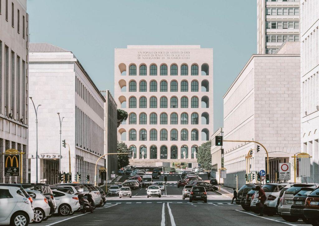 grande edificio quadrato con archi in fondo ad una strada
