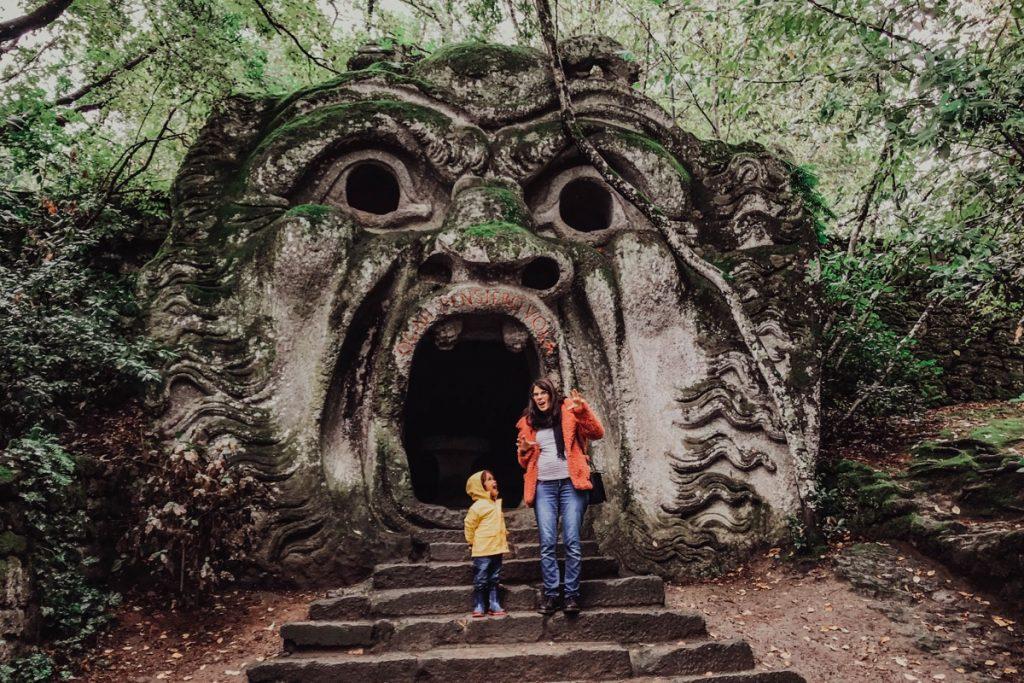 mamma e figlio davanti a scultura di un mostro nel parco dei mostri a bomarzo