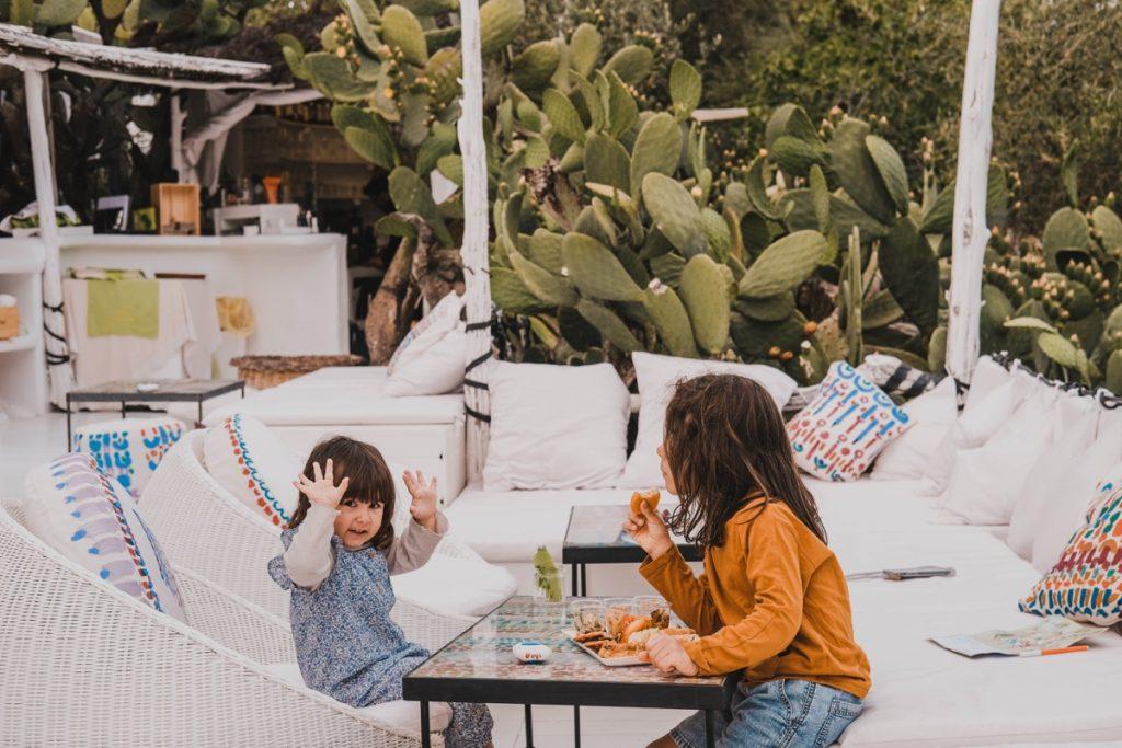 bambini seduti ai tavoli di terrazza circondata da fichi d'india