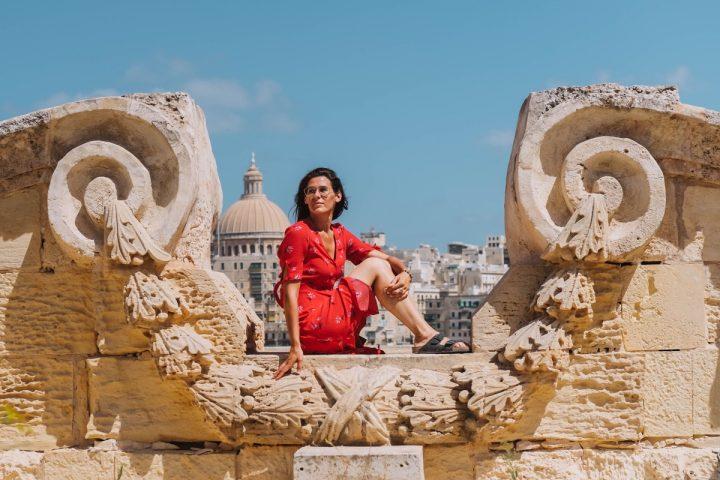 anna scrigni seduta su muro a Malta con vista alle spalla sulla città La Valletta