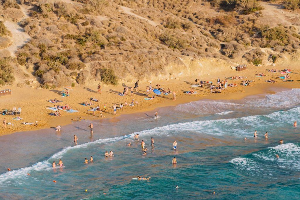 spiaggia a Malta con sabbia color arancione, onde e surfisti