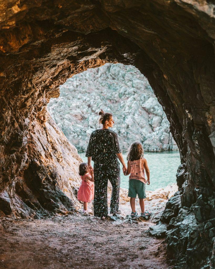 mamma e due bambini camminano attraverso un foro nella roccia