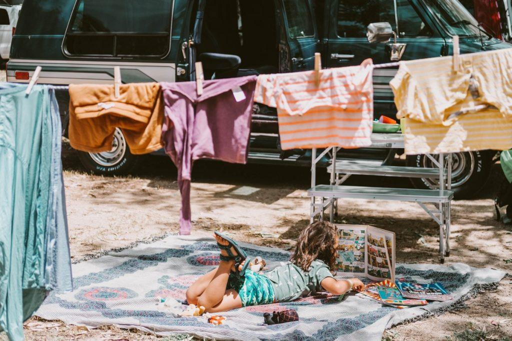 bambino disteso su un asciugamano davanti a camper che legge libro