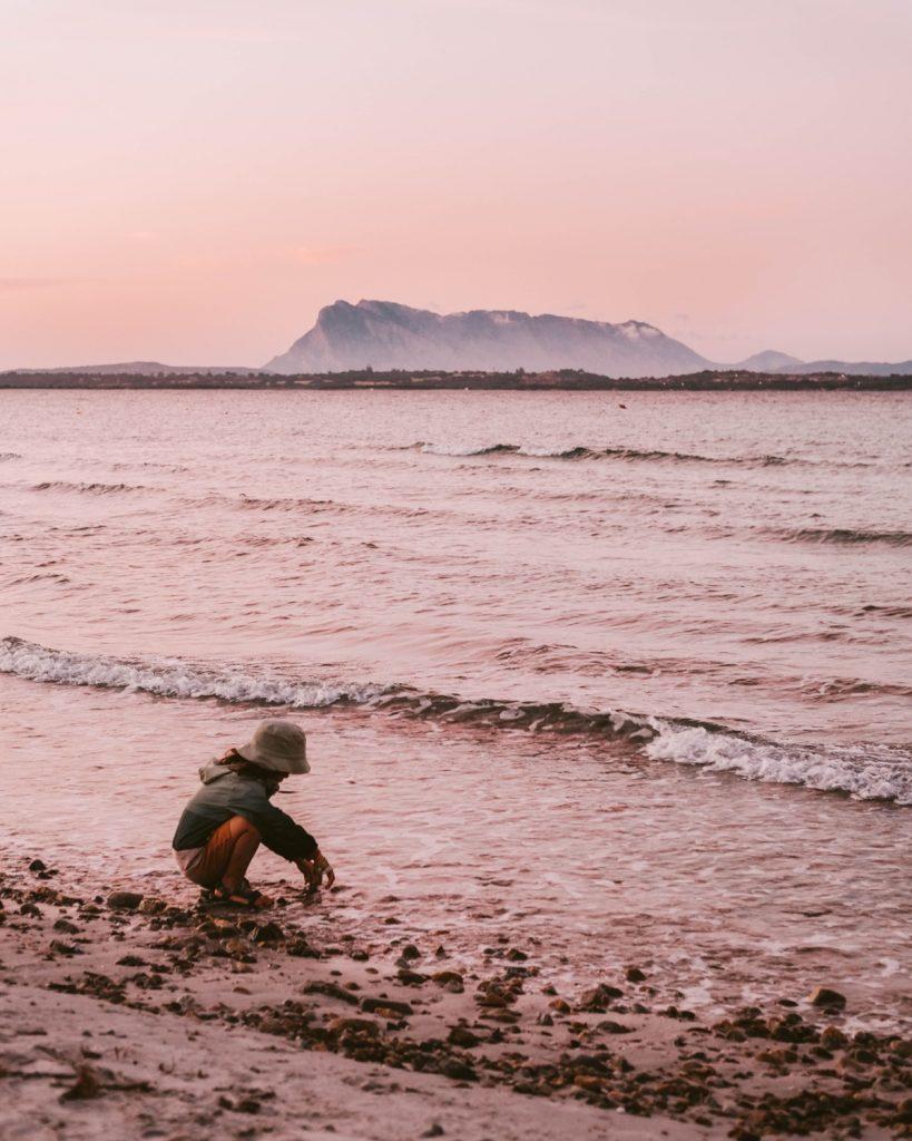 bambino che gioca sulla spiaggia al tramonto in Sardegna