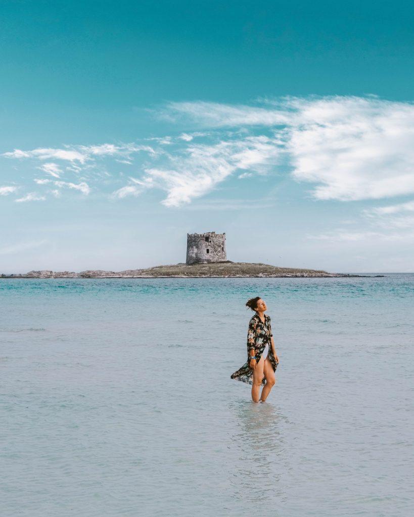 Mare color azzurro traparente con ragazza che cammina nell'acqua bassa, sullo sfondo antica torre di avvistamento