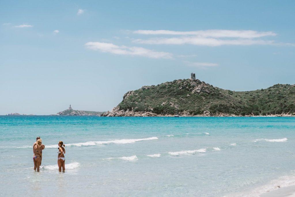 Porto Giunco in Sardegna: mare color turchese e collina con antica torre