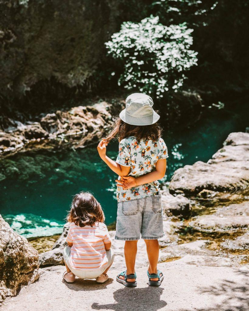due bambini di spalle ammirano l'acqua limpida di una sorgente