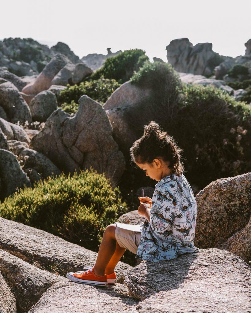 bambino disegna seduto sulle rocce