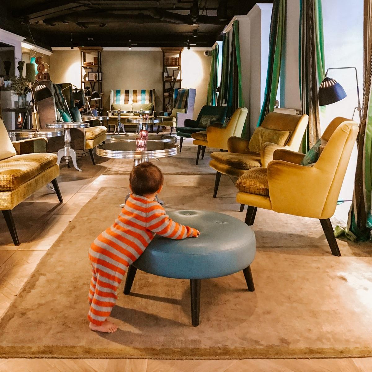 bambina piccola in hall di albergo appoggiata a sedia