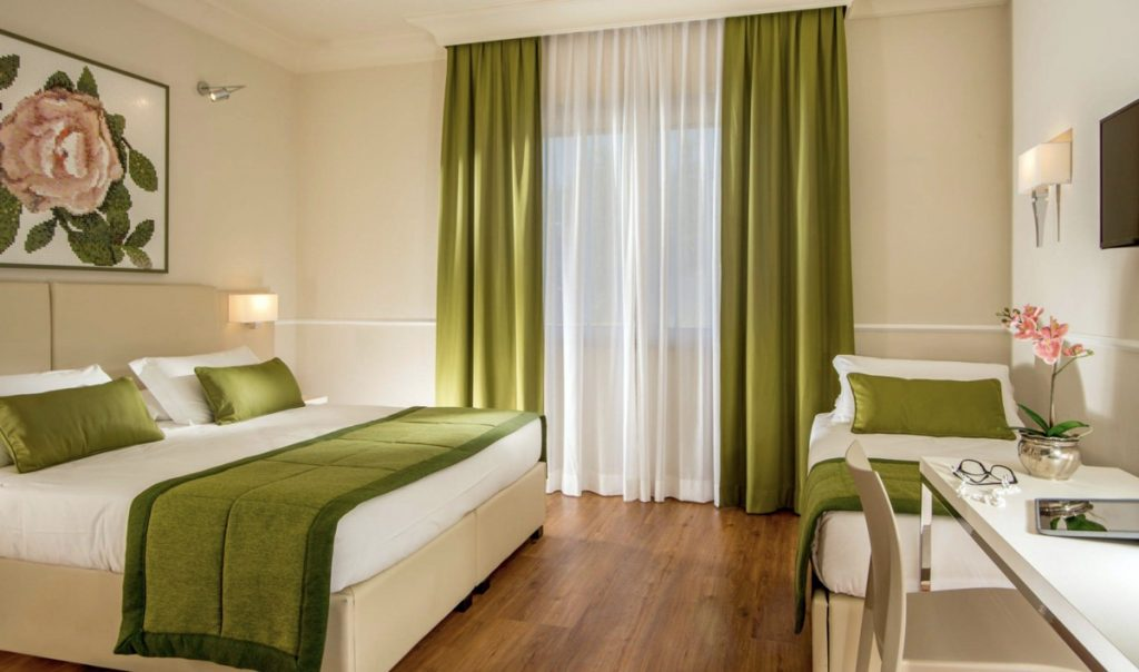 hotel a roma camera d'albergo con parquet e copriletto verde